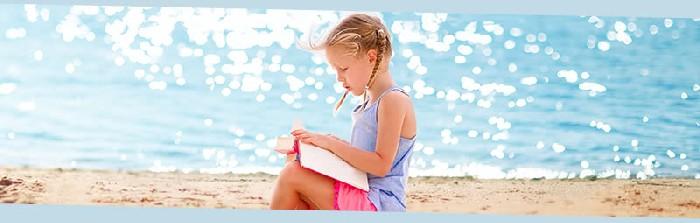 Bambina che legge in riva al mare