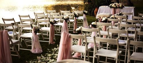 Allestimento in giardino con sedie bianche, fiori e tavolo cerimoniale